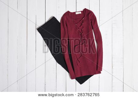 Clothes And Accessories. Black Midi Skirt And Red Sweater With Lacing On White Wooden Floor Planks.