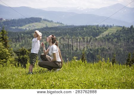 Mother And Little Son Blow Dandelion Against The Background Of Coniferous Forest And Mountains. Mate