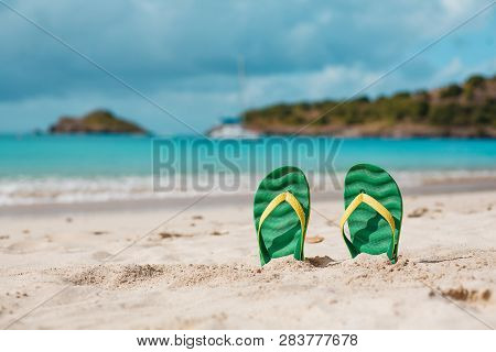 Green Flipflops In The White Sandy Beach Near Sea Waves, Nobody. Summer Vacation Concept With Blue W