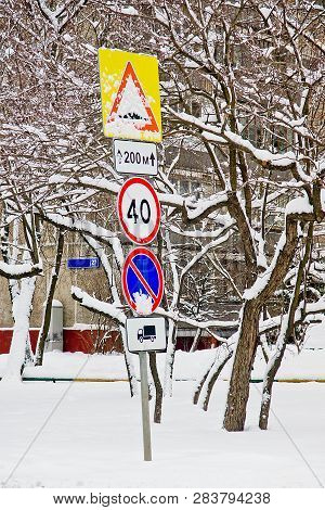Different Road Signs Under The Snow Near The Building