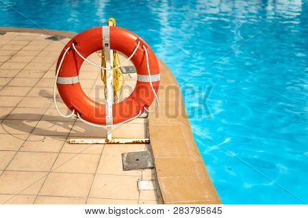 Lifebuoy Life Ring With Rope Attached To The Post Next To The Pool In City In Tropical Country