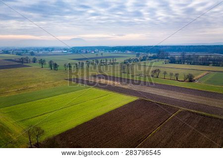 Aerial View On Rural Farmland In Slovenia, Europe, Vibrant Green Meadows And Brown, Ploughed Fields,