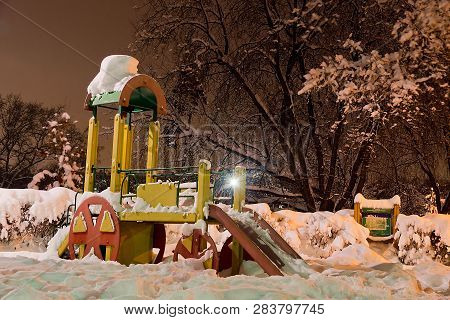 Playground Among The Snowdrifts In Winter City Park