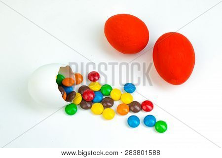 Happy Easter. Broken Easter Egg With Multi-colored Candy Decorations. On White Background. Copy Spac