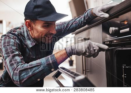 Dont Delay With Repair. Close-up Of Repairman Examining Oven