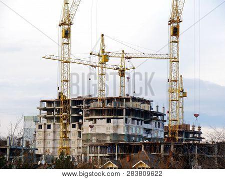 Five Tower Cranes At Construction Site. Concrete Building Under Construction.