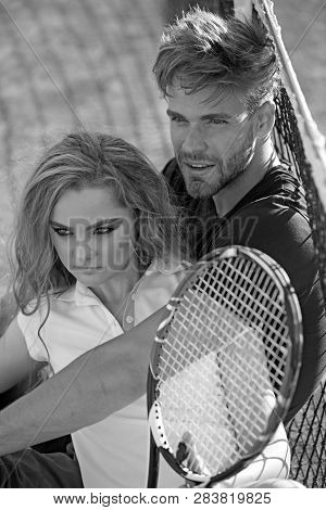 Tennis Players Rest On Court. Couple Relax On Tennis Court After Training. Sportsman And Sportswoman