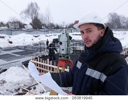 Bearded geodetic engineer-surveyor in white hardhat looks at the camera holding a drawing sheet against the construction site at the background poster