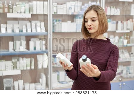 Pharmacy Customer Standing In Drugstore And Choosing Medical Products. Woman Looking At Cosmetic Whi