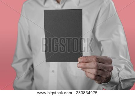 A Man In A White Shirt Holding A Black Booklet