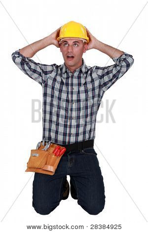 Astonished tradesman with his hands behind his head