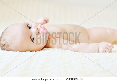 Happy Baby With Pacifier On The Bed