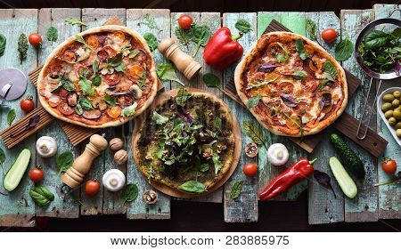 Flatlay Of Homemade Vegetarian Pizzas With Raw Ingredients On Shabby Blue Background. Pesto Pizza, M