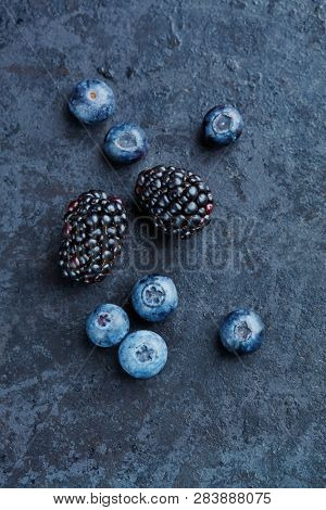 blueberries and blackberries on a dark surfce