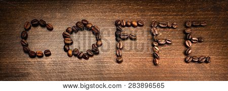 Coffe From Coffe Beans. Created Words Coffe On The Textured Wooden.