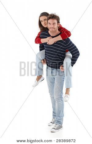 Loving young man carrying woman pickaback, smiling.?