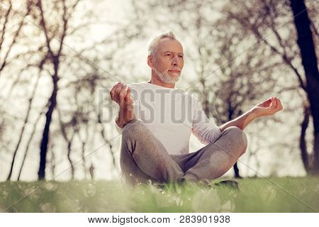 Relaxed Bearded Male Person Meditating On Nature