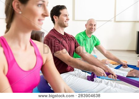 Smiling man with other people performing foot exercises with thera band in yoga class