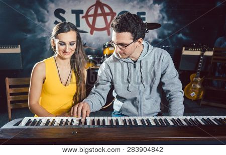 Piano teacher giving lessons to his student in music school
