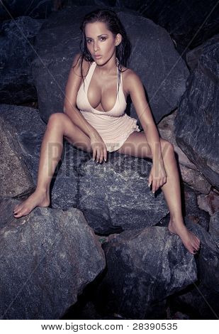 Beautiful Sexy Model On Rocks wearing a bathing costume showing her large breasts and with legs spread.