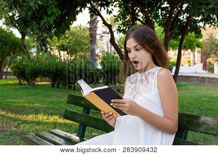 Closeup Portrait Of A Beautiful Surprised Girl With Wide Opened Eyes Who Is Reading A Book On The Be