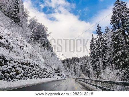 Beautiful winter scene with icy slick road driving situation alpine road covered with water and ice and snowy trees all around