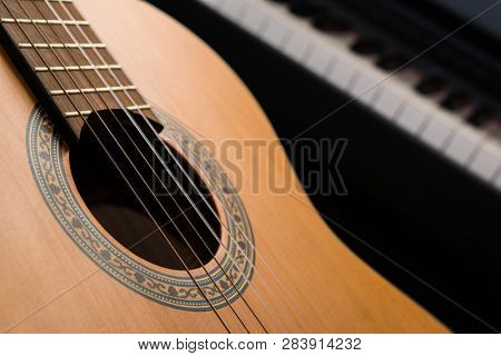 Guitar closeup, piano in the background