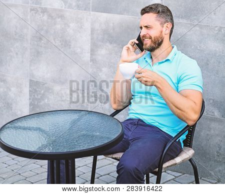 Coffee break brings physical and mental wellbeing. Brief coffee break provides employees with quick ways to relax. Man sit terrace and drink cappuccino speak phone grey wall background. Time to relax poster