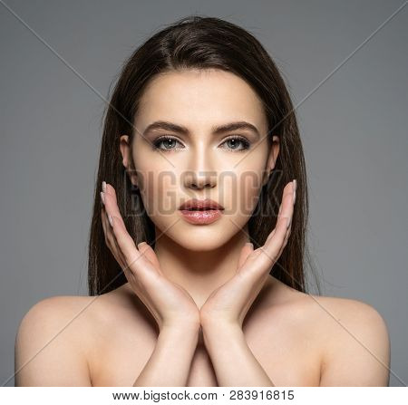 Portrait of beautiful young brunette woman with clean face. Front portrait of beautiful girl with beautiful blue eyes and face - on white background