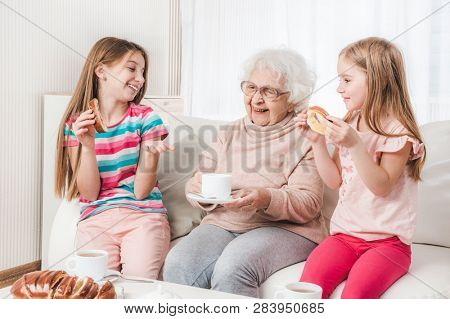 Smiling great-grandmother with granddaughters having tea poster