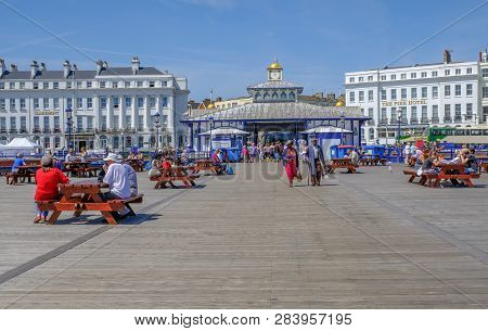 Eastbourne, Sussex, England, Uk - August 1, 2018: People Strolling And Sitting On Picnic Benches Nea