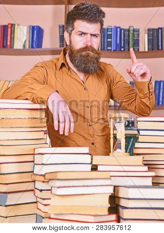 Man On Confident Face Stands Between Piles Of Books, While Studying In Library, Bookshelves On Backg