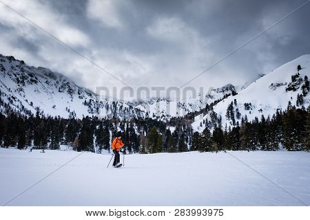 Man With Orange Jacket Snowshoeing On Snow Covered Scheibelalm In Holiday Resort Hohentauern With Pa