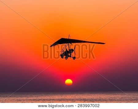 The Person Flying On A Trike With The Motor Against The Hang-glider Is Flying Against The Sunset.