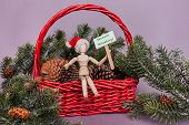 Merry christmas happy holidays greetings on picket sign held by wooden jointed manikin doll sitting in big red basket filled with pinecones and greenery on solid background poster