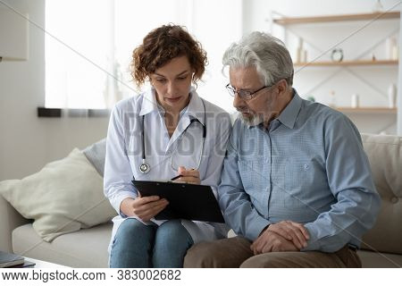 Young Woman Doctor Nurse Consulting Mature Patient During Homecare Visit
