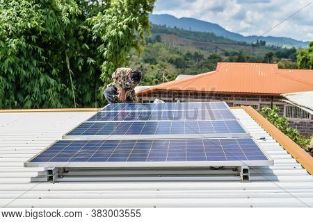 Man Installing Solar Panels On A Roof House For Alternative Energy Photovoltaic Safe Energy. Power F