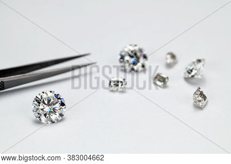 Diamonds And Jewelry Tweezers On White Background