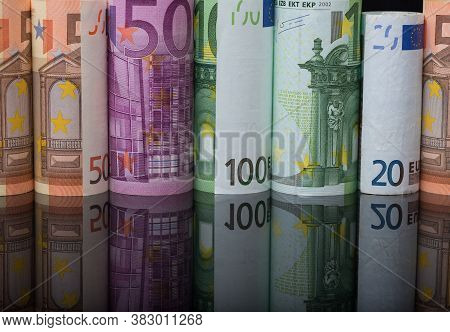 Different Euro Banknotes Rolled Up With Reflection On Background. European Union Currency Cash Bill.
