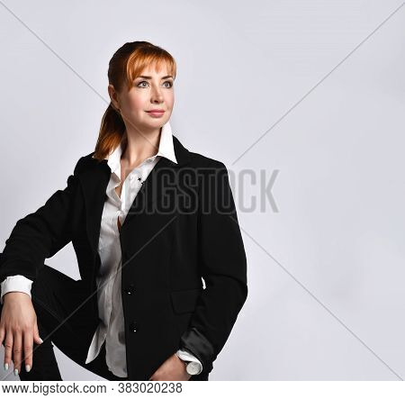 Modern Pensive Redhead Woman Wearing A Black Jacket, White Shirt And Jeans Posing Sitting On A Chair