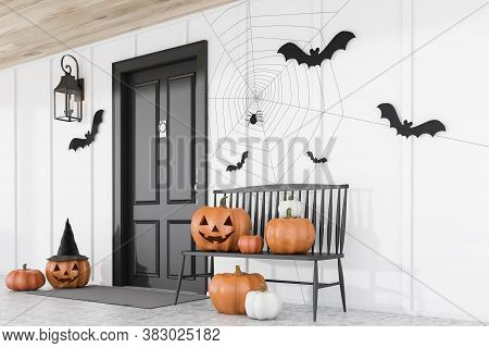 Carved Pumpkins, Bats And Spiders Near Black Front Door Of Modern House With White Walls And Black B