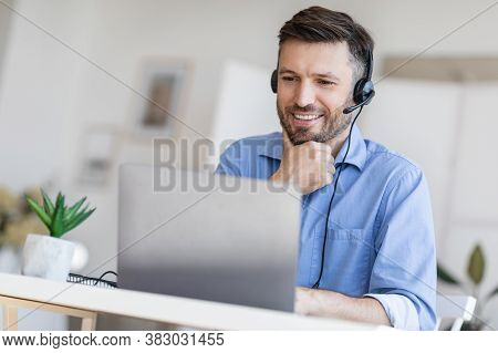 Hotline Support Service. Handsome Male Call Center Operator In Headset Working With Laptop In Modern