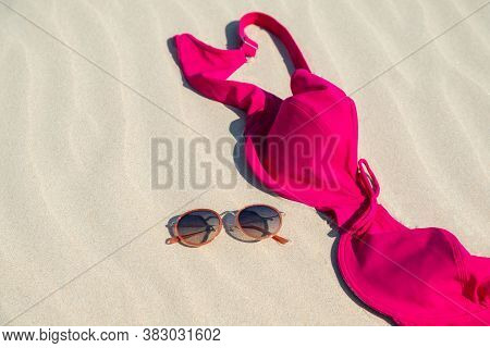 Close Up Of Woman Bra And Glasses On The Sand. Concept Of Sunbathing Naked On The Nude Beach. Natura