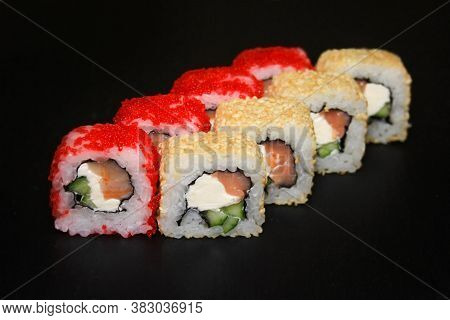 Set Of Sushi Rolls With Masago And Sesame Caviar Stuffed With Salmon And Cheese On A Black Backgroun