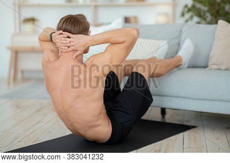 Morning Exercise For Vitality. Sporty Guy Doing Exercises For Press, Puts Feet On Sofa On Mat In Liv