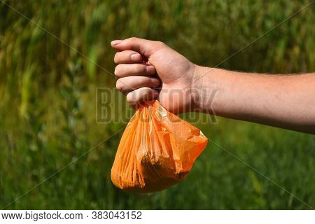 An Image Of An Out Stretched Hand Holding A Orange Plastic Dog Poop Bag Full Of Dog Poop And Ready F