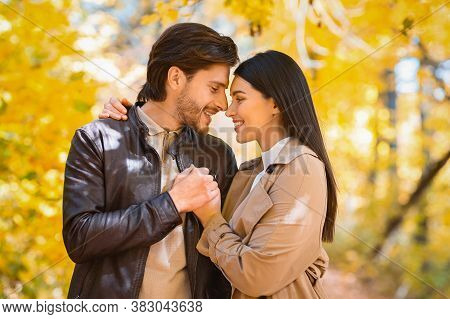 Couple Embracing, Holding Hands And Looking At Each Other Over Golden Autumn Trees, Copy Space