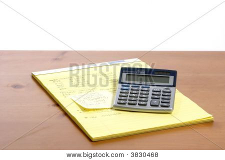 A calculator on a legal pad in an office poster