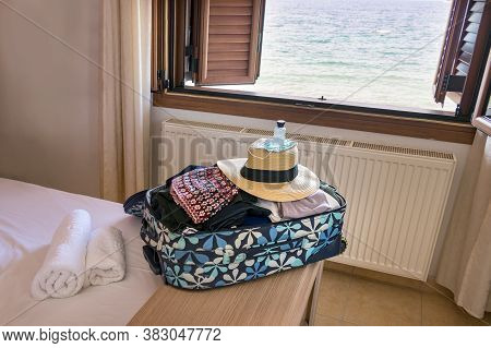 A Travel Bag With Female Clothes, Straw Hat, Mask, Hand Sanitiser Over A Hotel Room. Travel Safely C