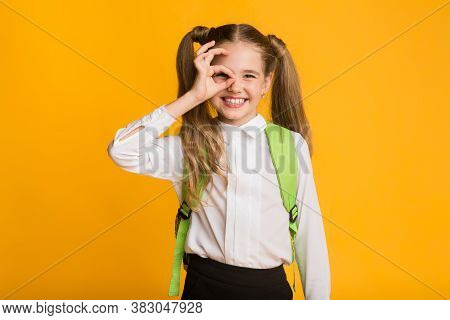 Everythings Ok. Funny Schoolgirl Gesturing Okay Sign Near Face Looking At Camera Standing Over Yello